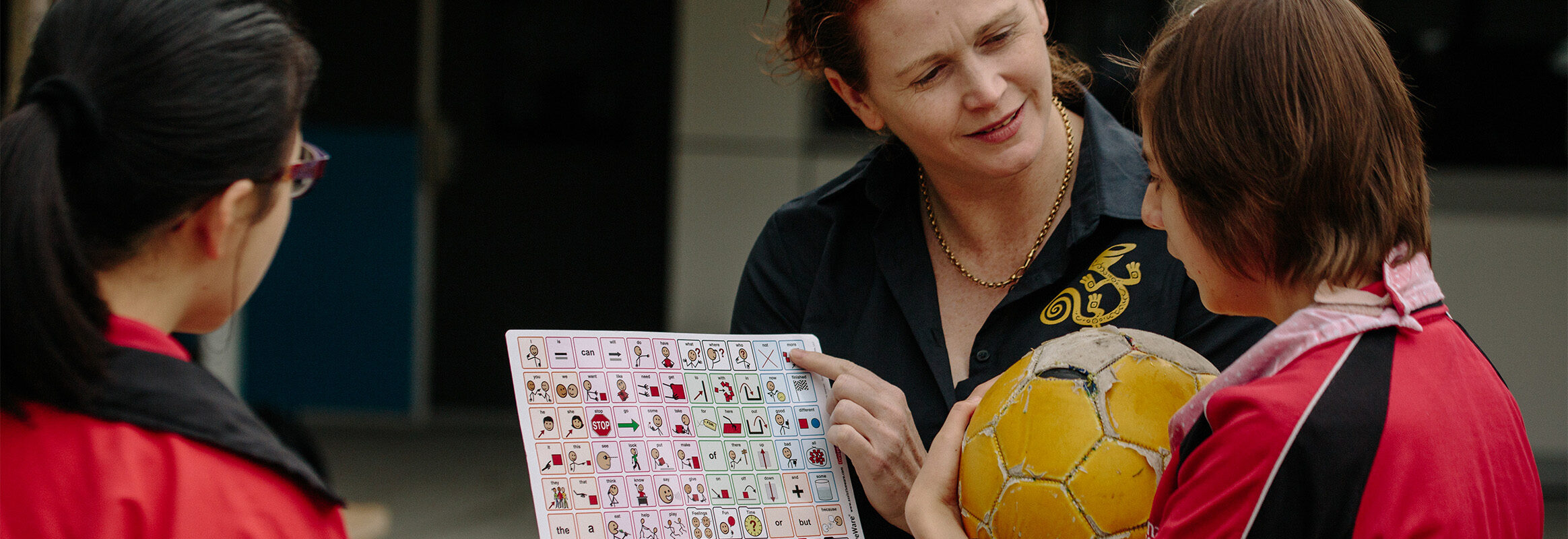 Young girl with soccer ball learning with core words board