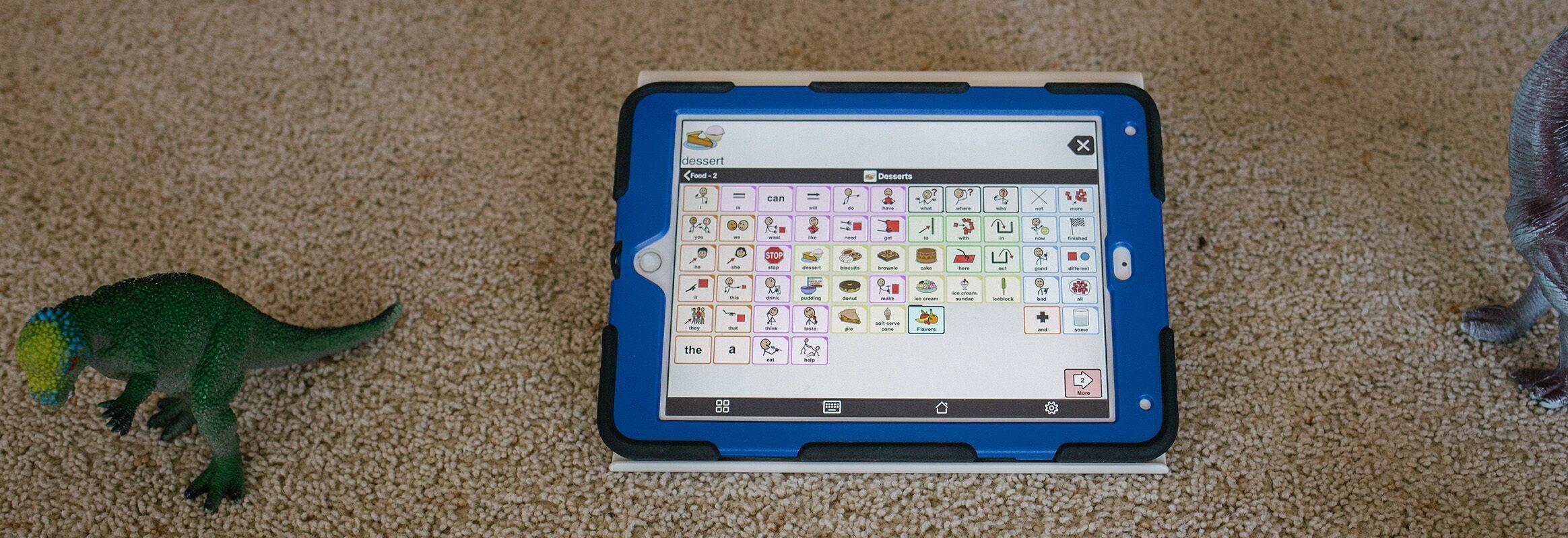 iPad met Proloquo2Go 11x7 rooster op tapijt met speeltjes ernaast.