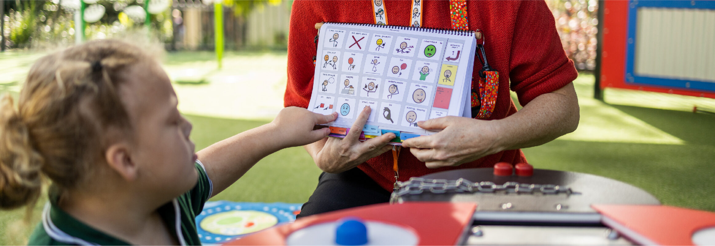 Girl pointing at symbol in PODD book while teacher holds the book