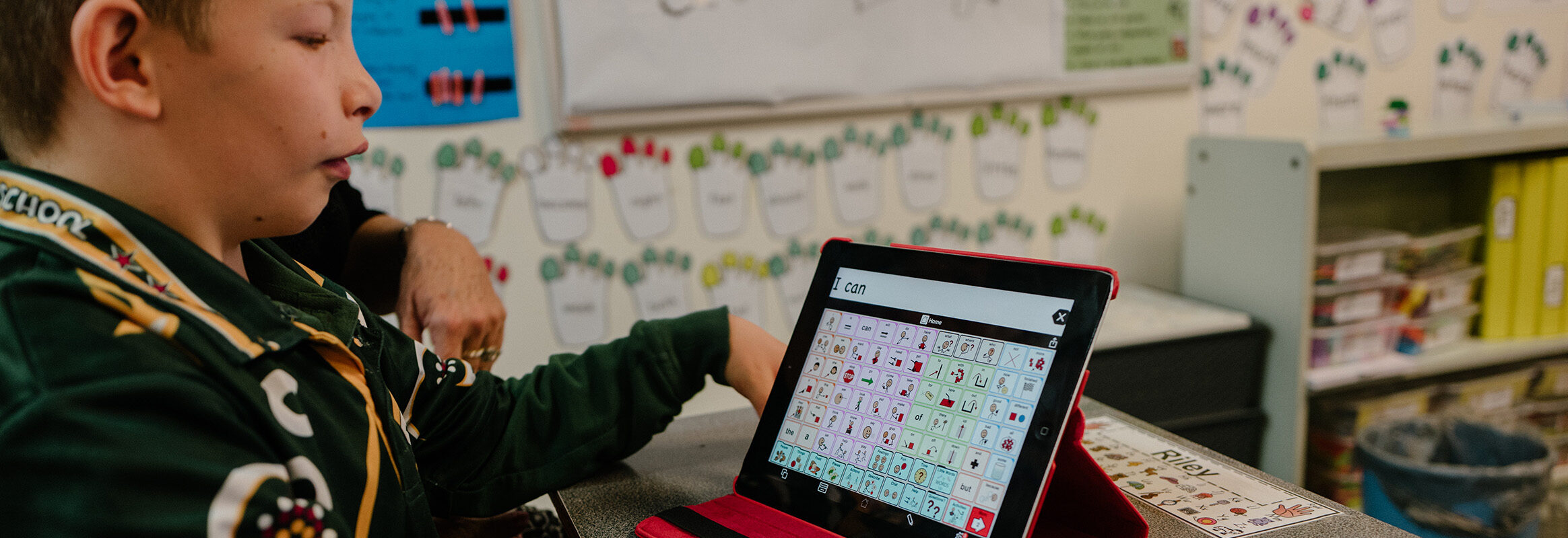 Young boy in classroom learning with iPad AAC System