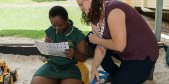 Amanda, buiten in een zandbak met een leerling, wijzend naar een kernwoordenbord in haar hand.