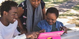 Woman, young man and child smiling and looking and pointing at iPad in a park