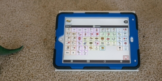 iPad with Proloquo2Go on carpet surrounded by toys