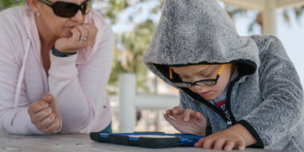 Young boy using iPad outside