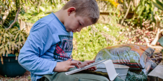 Young boy sitting outside using iPad