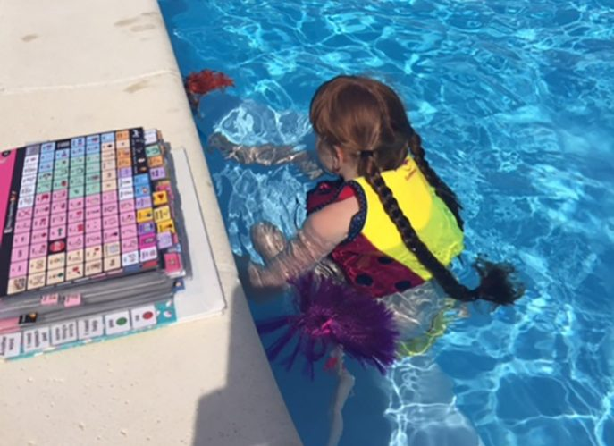 Photo of a child in a pool with an AAC book on the edge