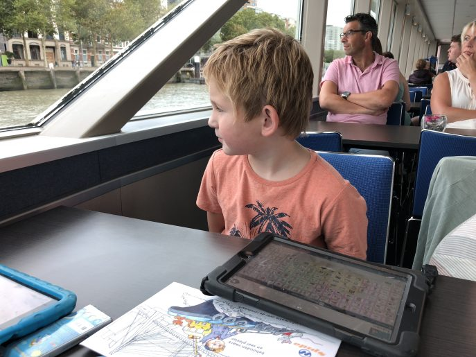 Hugo in a canal boat looking at the window, an iPad with Proloquo2Go on the table in front of him