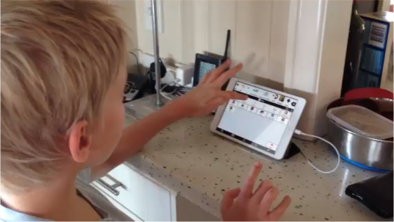 Boy using AAC system on iPad