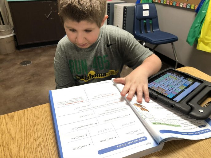 The author's son using a workbook and Proloquo2Go on an iPad