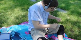 Boy in on grass field listening through headphones