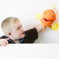 Boy holding orange fish hand puppet