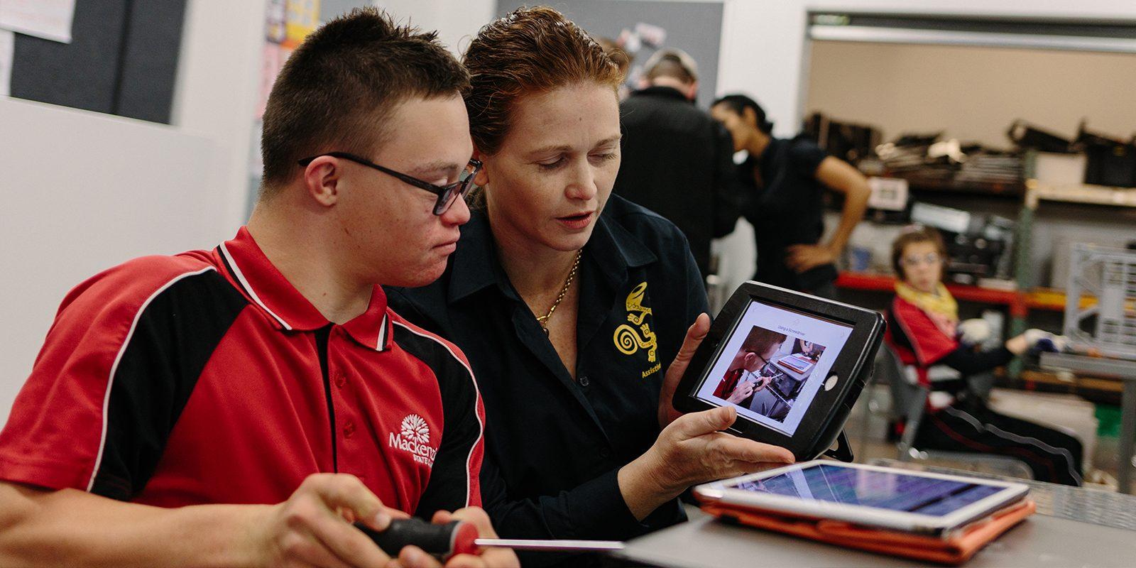 Lerares toont iPad aan leerling