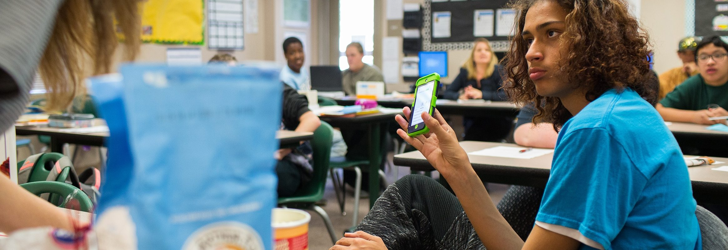 Boy using iPhone in classroom
