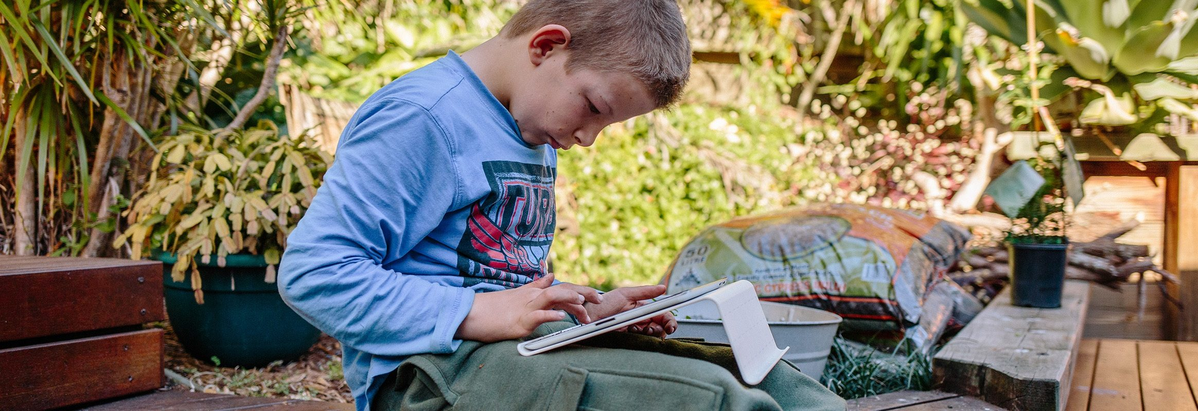 Boy in garden with iPad