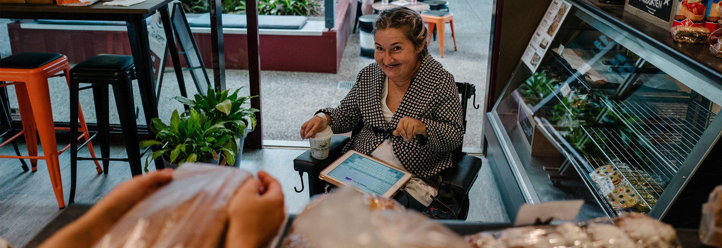 Femme en commande de boulangerie avec iPad Proloquo4Text