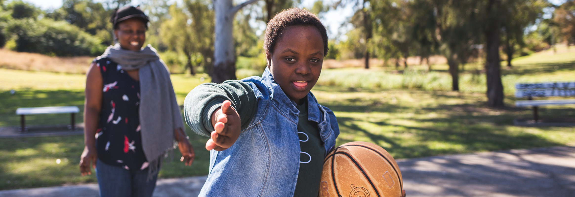 Bonita, a Malawian teenage girl on the basketball court, gesturing to the camera, with another black woman on the court in the background