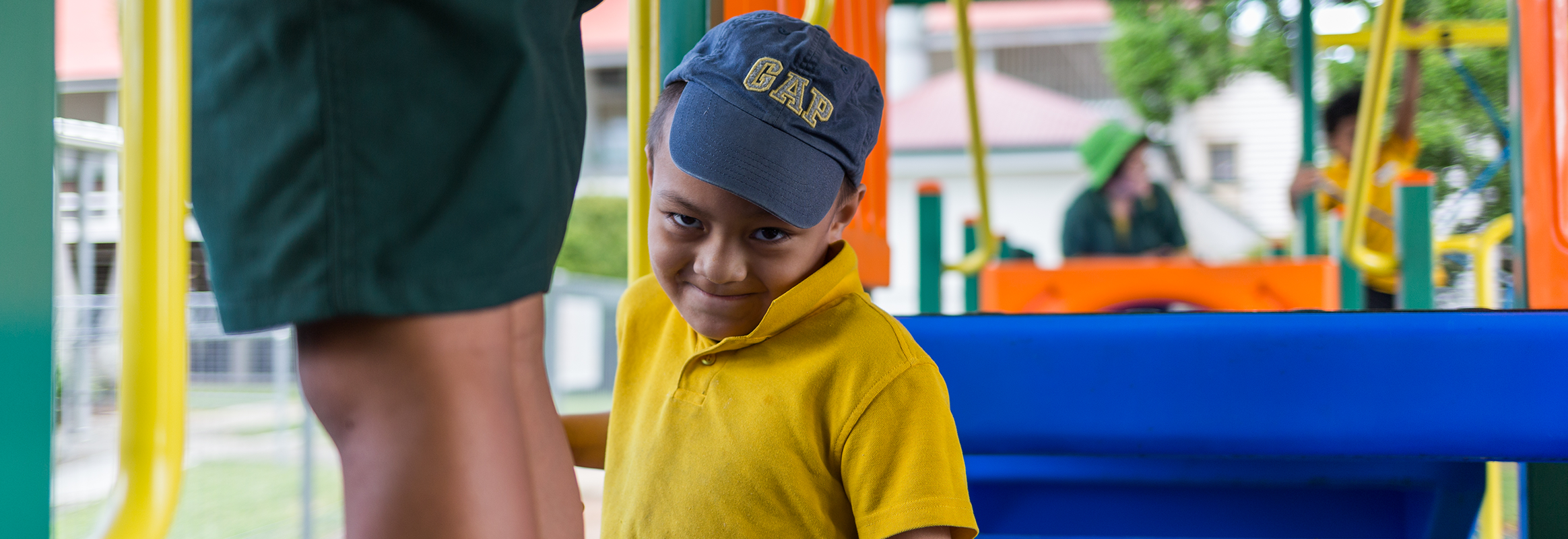 Monty, a young Samoan boy on a playground, smiling at the camera