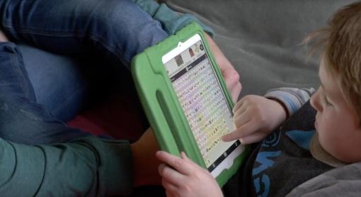 Hugo op de bank met vader en iPad