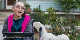 Elina, een blanke vrouw in een rolstoel met een iPad en een hond aan haar zijde