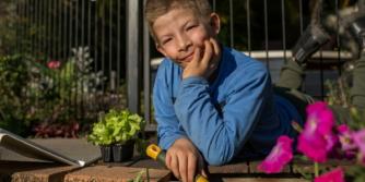 Tom, un adolescent blanc couché et travaillant dans le jardin avec un iPad à ses côtés