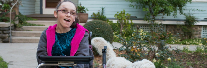 Elina, a white woman in a wheelchair with an iPad and a dog at her side