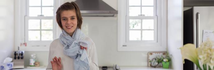 Lara, een jonge blanke vrouw in een lichte keuken, met uitzicht op de camera en glimlachend