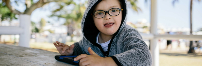 Lucas, a small white boy in a hoodie sitting outside, using an iPad and smiling