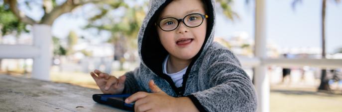Lucas, een kleine blanke jongen in een hoodie die buiten zit, een iPad gebruikt en lacht