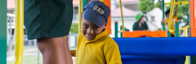 Monty, een jonge Samoaanse jongen op een speelplaats, glimlachend naar de camera